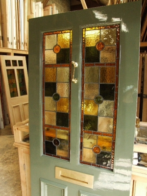 A pretty stained glass 2 glazed panel door with pastel greens and ambers stained glass