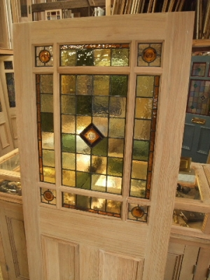 A lovely stained glass internal door incorporating pastel green and amber stained glass with amber rondels
